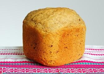 Свежеиспечённый хлеб на белом, с красным орнаментом, полотенце