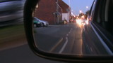 Side mirror view of night street