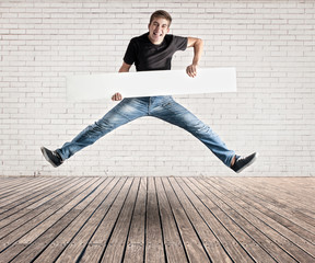 attractive young man jumping with a white banner