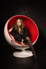 Sexual woman sitting in a red ball-chair
