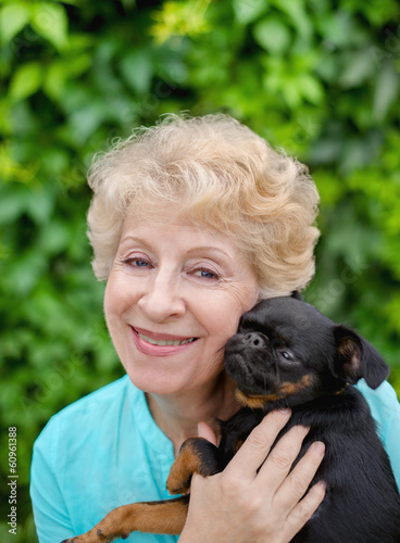 Beautiful smiling senior woman with small dog in the summer park