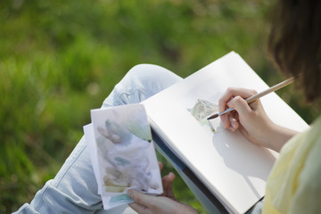 Teen artist painting with watercolour paint outdoor.