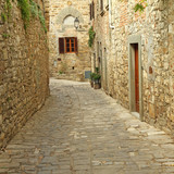 narrow  paved street and stone walls in italian village