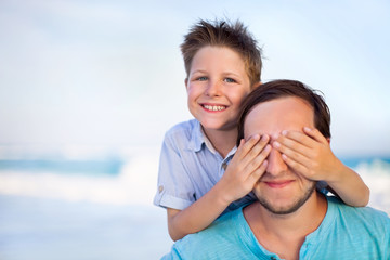 Boy Covering Father's Eyes At Beach