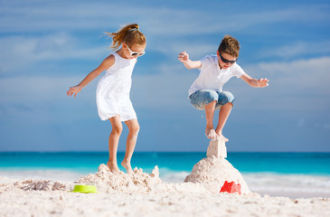 Two kids crushing sandcastle