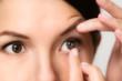 canvas print picture - Eine Frau setzt sich eine Kontaktlinse ein
