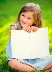 Adorable little girl reading book