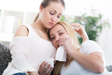 Friend comforting her crying friend at home