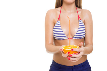 Fit young woman in bikini holding orange fruit