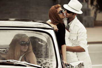 Young couple in love and jealous girl in a retro car
