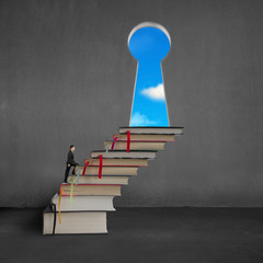 Businessman climbing on stack books to key shape door