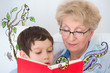 Grandmother and little boy reading book happy together at home.