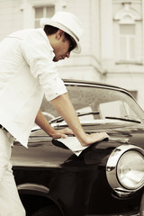 Young man reading a road map on the retro car