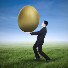 Businessman holding a golden egg