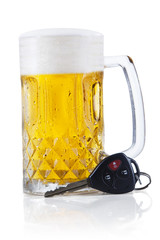 Car key lying next to a full glass of beer