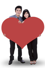 Couple in love holding a big red heart