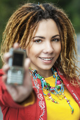 woman with dreadlocks showing mobile phone