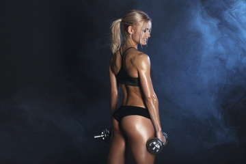 strong sexy woman is training with dumbbells