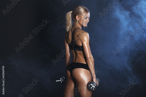 strong sexy woman is training with dumbbells - 60969149