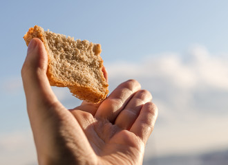 Hand hold a slice of bread over sky background.