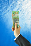 Hand holding money - Australian dollars - in blue sky background