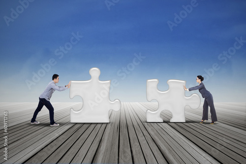 Two business people put two puzzles
