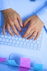 Female hands typing on white computer keyboard