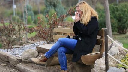 attractice blonde women sneezing outdoors