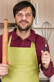 Smiling young man with apron holding a beater and a rolling pin