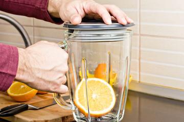 Closeup of a man preparing orange juice