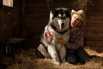 Young woman with a big dog in a barn on straw