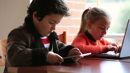 smart children studying, using digital tablet and laptop