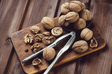 Walnuts and nutcracker on a wooden chopping board