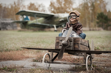 Young boy-pilot in the plane at the airport handmade autumn