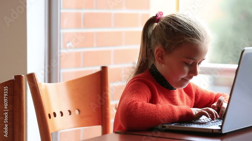 smart cute blonde child studying, using laptop at classroom
