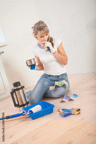 beautiful female painter sitting on wooden floor and thinking