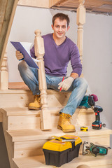 young carpenter sitting on step of of ladder with tools