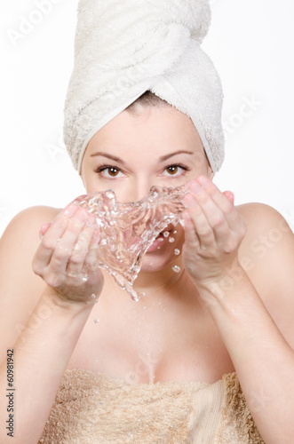 Young woman washing her face with water