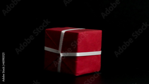Red Gift Box with White Ribbon, spinning - Low key studio shot