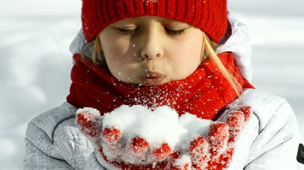 little girl blows snow from hands, slow motion
