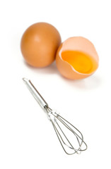 whisk and eggs isolated on white