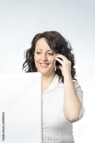 Young woman in front of laptop talking on the phone
