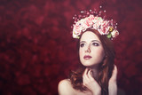 Beautiful redhead women with wreath on red backgrund.