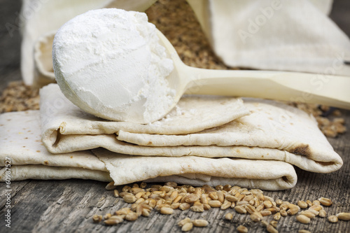 Pita bread with grains and flour on wooden table