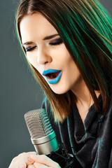 Beautiful young woman singer. Emotional teen girl