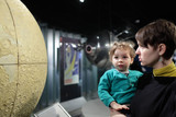 Mother with son looking at globe of moon