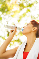Fitness woman with bottle and towel
