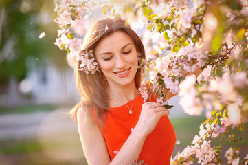 Young woman in red dress standing among blossom trees