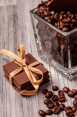 Thin chocolate with a ribbon and a jar of coffee beans