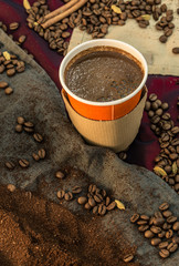 Coffee in a paper cup with beans and ground coffee